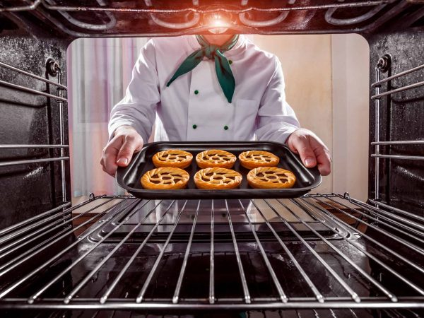 45105392 – chef prepares pastries in the oven, view from the inside of the oven. cooking in the oven.