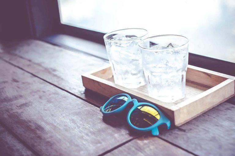 2 Wassergläser auf Tablett hinter Sonnenbrille