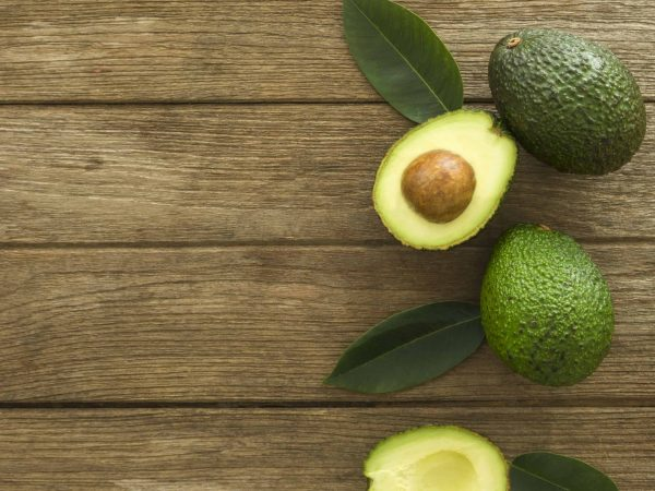 avocado and Sliced avocado slices on a dark wood background.