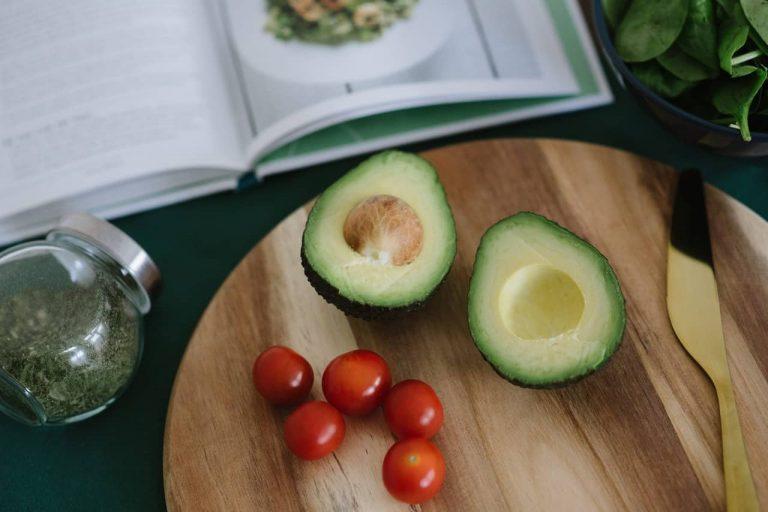 aufgeschnittene Avocado auf Schneidebrett neben Kochbuch