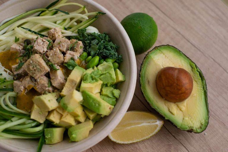 Avocado neben Teller mit Gericht