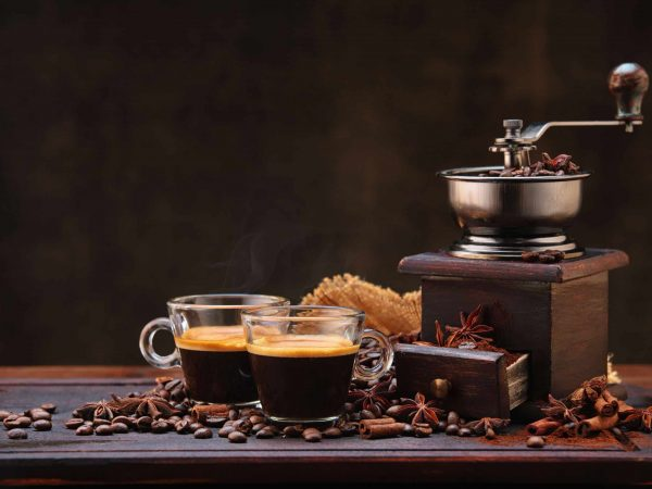 Coffee beans and grinder on wooden table  with cinnamon and anise stars.
