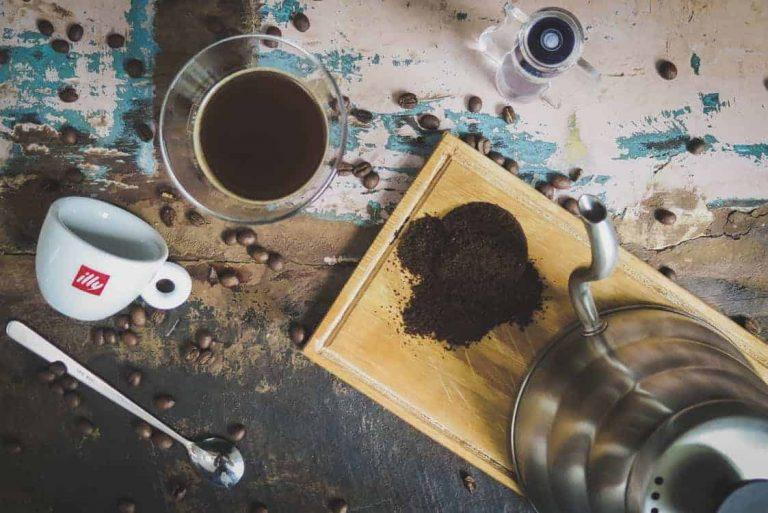 Kanne, Glas und Tasse mit Kaffeebohnen