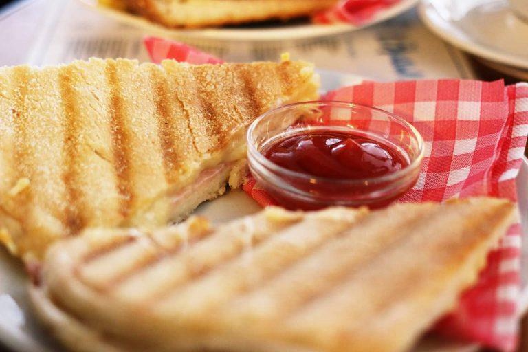 Zwei Schinken Käse Panininis auf einem Teller mit einer kleinen Schüssel voll Ketchup und einer Serviette