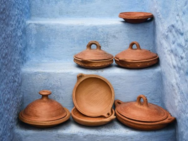 Empty traditional moroccan tagine (tajine) on blue painted stairs.