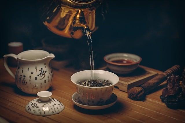 Tee wird aus Teekanne in Tasse gefüllt