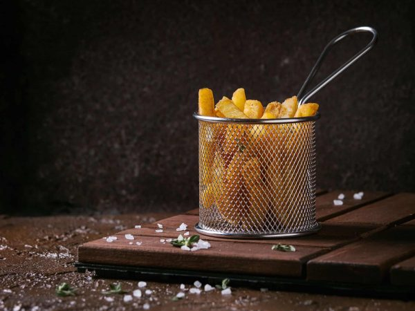 Traditional french fries potatoes served in frying basket with salt, thyme on wooden board over brown texture background. Homemade fast food
