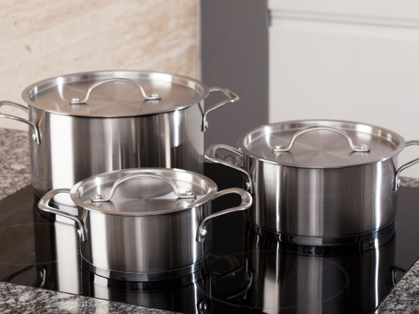New cookware set on black induction hob in modern kitchen