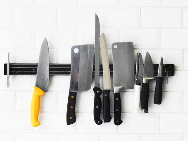 Set of knifes hanging on the white wall