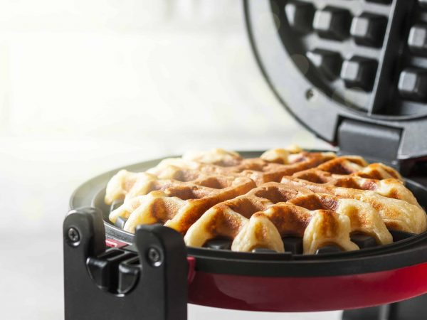 The process of making homemade waffles. Freshly baked waffles in a waffle iron. Selective focus