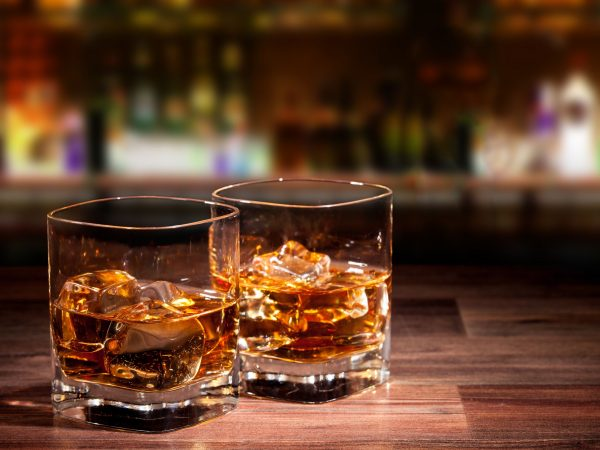 21187859 – whiskey drinks on wooden table with blur bar on background