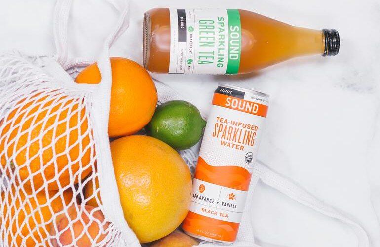 Einkaufsnetz gefüllt mit Orangen, 1 Limette und 2 Getränken.