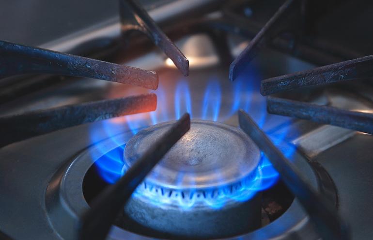Kochfeld eines Gasherdes mit blauen Flammen