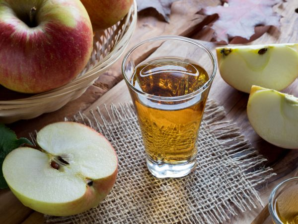 89257380 – apple cider vinegar in a glass on a wooden table, with apples in the background
