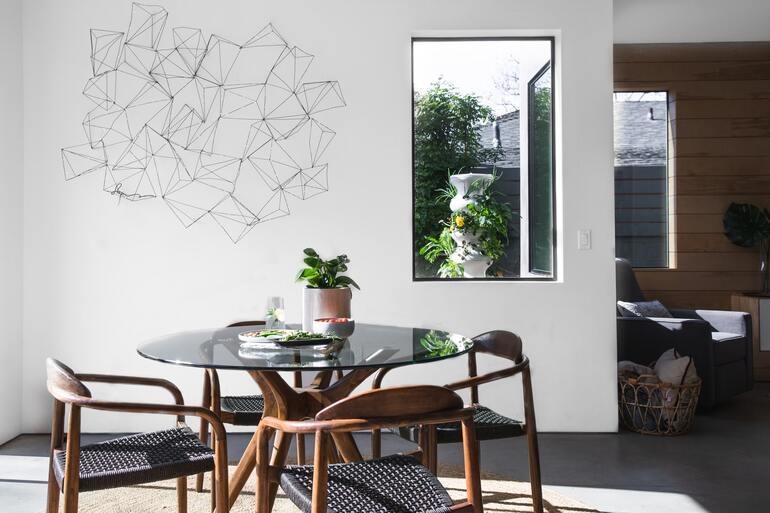 runder Esstisch mit Tischplatte aus dunklem Glas, 4 Stühle in dunklem Holz, Pflanze auf dem Tisch, Wand Art im Hintergrund auf weißer Wand, Fenster in den garten