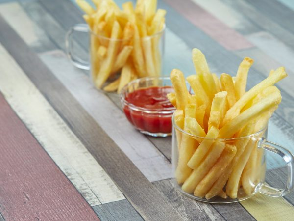 French fries are served in two glass mugs and a portion of ketchup, on a wooden surface painted in different colors. Diagonal composition.