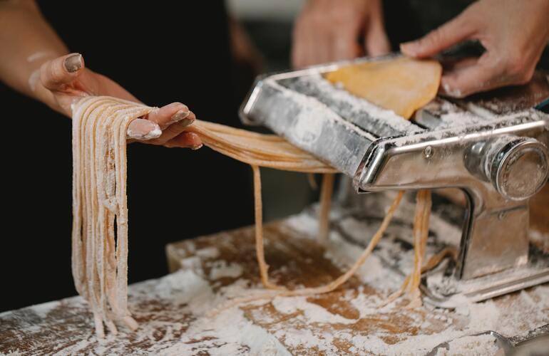 Das Bild zeigt zwei Menschen, die gerade Nudeln mithilfe einer elektrischen Pastamaschine zubereiten.