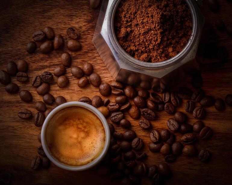 Tasse mit Kaffee, gefüllter Behälter mit gemahlenen Kaffeepulver, verstreute Kaffeebohne auf einem Holztisch.