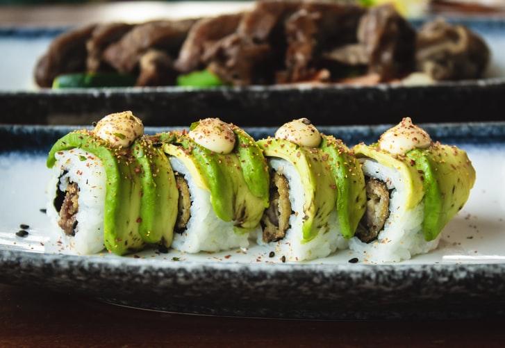 Auf dem Bild sind schön zubereitete Sushirollen mit Avocado zu sehen.